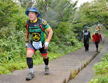悪天候の中、高山植物などを楽しみながら約3キロの登山に挑む参加者=秋田県にかほ市