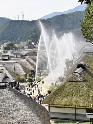 かやぶき屋根の町並みに描かれた水のアーチ=大内宿