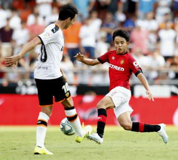 バレンシア戦の後半に途中出場し、スペインでの公式戦デビューを果たしたマジョルカの久保建(右)=バレンシア(共同)