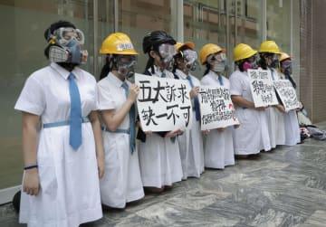 ヘルメットとガスマスクを着け、学校前で抗議活動する生徒ら=2日、香港(AP=共同)