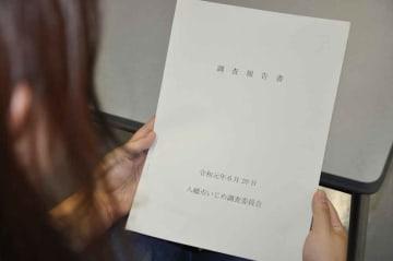 いじめ調査委員会の報告書を持つ被害生徒の母親