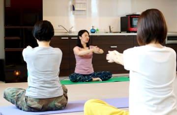 深い呼吸とストレッチで体を動かすサバイバーエクササイズを教える山田さん(中央)=大村市杭出津1丁目、おおむら海辺のクリニック