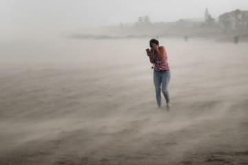 ハリケーン「ドリアン」により吹き荒れる風や砂の中、ビーチを歩く女性=2日、米南部フロリダ州(ゲッティ=共同)