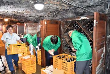 龍泉洞内の貯蔵庫で熟成した日本酒を丁寧に搬出する従業員ら