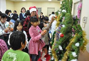 田島さんと一緒にクリスマスツリーを飾り付ける子どもたち