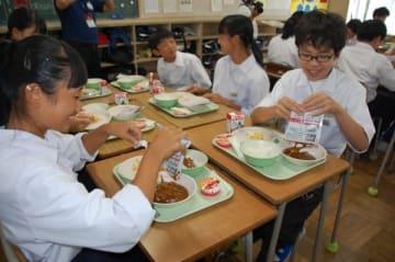 【防災給食で備蓄食材のヒートレスカレーを食べる生徒ら=鈴鹿市加佐登3丁目の市立白鳥中学校で】