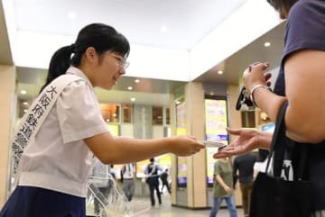 悪質な痴漢行為の追放を呼び掛ける高校生(左)=3日、JR天王寺駅
