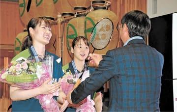 穂積市長から祝福の花束を受け取り、お返しにラケットを贈る永原(中央)、松本のペア