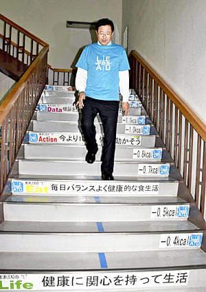 メッセージが掲示された階段を下りる室井市長