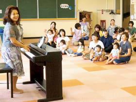 菅原さん(左)の歌と演奏を楽しむ親子ら