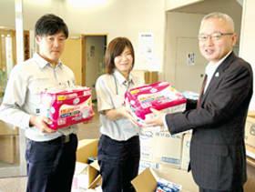 米野事務局長(右)に善意を手渡す北藤さん(左)と井川さん