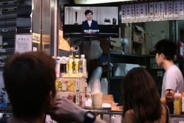 Anthony Wallace / AFP=時事 テレビで放送された映像を、食堂で見る香港市民