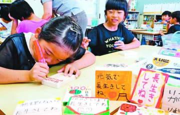町産ヒノキの木片にメッセージを書く神領小の児童=神山町神領の同校