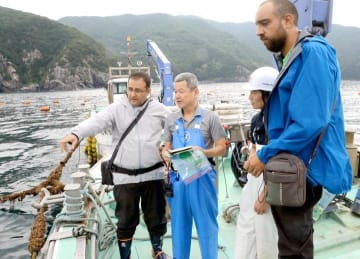 通訳者を挟んで安岡高身社長(右から2人目)にいけすの構造を質問するヤッサール・サケルさん(左)とハビブ・アッバスさん(右)=8月31日午前、愛南町