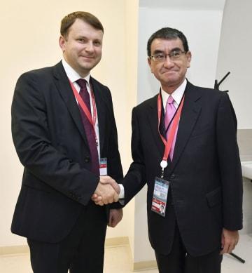 会談前にロシアのオレシキン経済発展相(左)と握手する河野外相=5日、ロシア・ウラジオストク(共同)