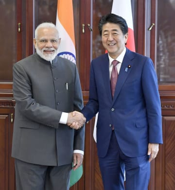 会談に先立ち、インドのモディ首相(左)と握手する安倍首相=5日、ロシア・ウラジオストク(共同)