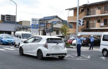 交差点に立ち、手信号で車を誘導する岡山中央署員=岡山市中区浜(画像の一部を加工しています)
