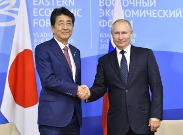 会談前、握手するロシアのプーチン大統領(右)と安倍首相=5日、ロシア・ウラジオストク(共同)