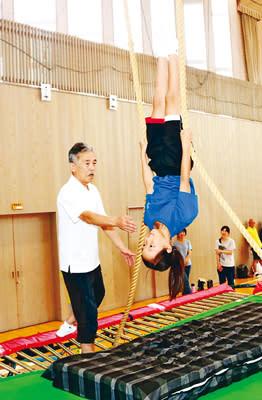 モーグルのエア演技の感覚を磨くため、児童にトランポリンを指導する池田さん(左)