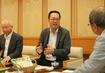 「県産品のPRにも貢献したい」と語る木下裕亮代表取締役(中央)=県庁