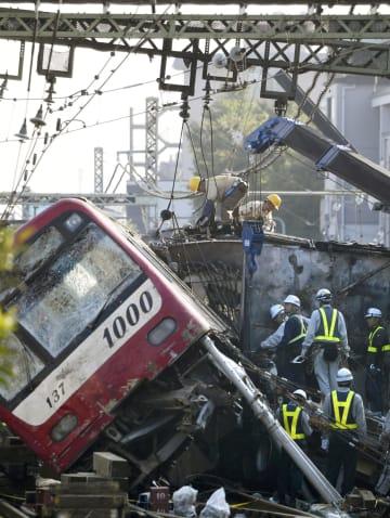 京浜急行の電車がトラックと衝突、脱線した事故現場で続く復旧作業=6日午前6時51分、横浜市神奈川区