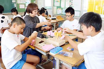 芝井支部長の指導を受け、指人形を作る児童=小矢部市津沢小学校