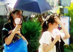携帯扇風機を手に夏を乗り切る女性=神戸市中央区