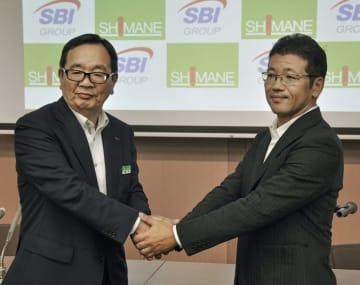 資本業務提携を発表し、握手する島根銀行の鈴木良夫頭取(左)とSBIホールディングスの森田俊平専務=6日、松江市