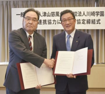 協定書を手に握手を交わす川崎理事長(右)と藤木理事長