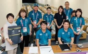 ラグビーW杯日本大会に向けて、公式ボランティアにユニホームなどを配布。ユニホームを着て、グッズを配布したスタッフ=6日、大分市の昭和電工ドーム大分
