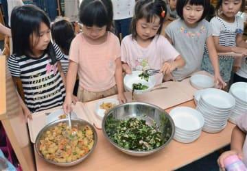 給食のおかずを皿に取る園児=秋田市