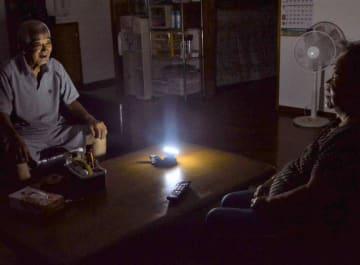 停電の中、電灯の明かり一つで夜を過ごすお年寄り=6日午後8時50分ごろ、宮古島市平良西里