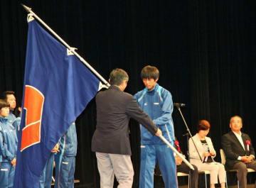 和歌山県選手団長の仁坂吉伸知事(左)から団旗を受け取る旗手の中野智稀君=和歌山市で