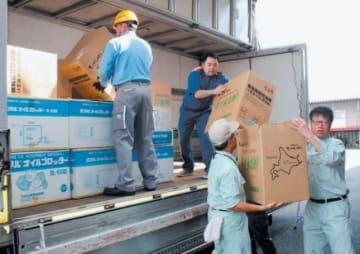 オイル吸着マットの入った箱をトラックに積み込む大分県の関係者ら=7日午前、大分市