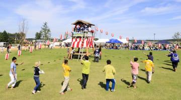 福島県大熊町で行われた夏祭りで盆踊りを踊る人たち=7日午後