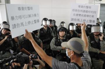 香港国際空港に近い地下鉄の駅で警察官(奥)に抗議する男性=7日(共同)
