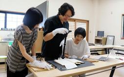 山田風太郎さんの創作ノートやメモなどをデジタルカメラで撮影し、データ化に取り組む研究者ら=山田風太郎記念館