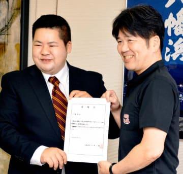大城市長(右)から委嘱状を受け取った仁禮さん