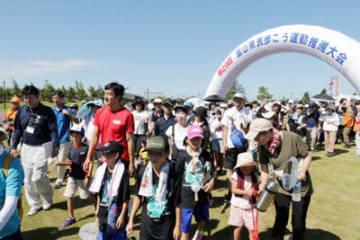 朝原さん(赤いシャツ)と共に出発する参加者=滑川市スポーツ・健康の森公園陸上競技場