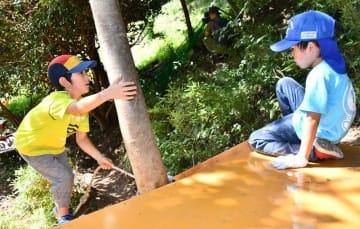 ロープを使って滑り台をよじ登る子どもたち