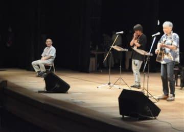 自ら詠んだ詩の楽曲をステージ上で聴く胎児性水俣病患者の永本賢二さん(左)=水俣市