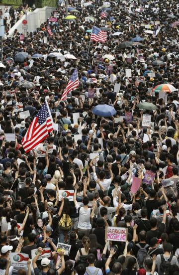 香港当局者への制裁法案を米議会が早期に可決するよう求め、香港中心部でデモ行進する市民ら=8日(共同)
