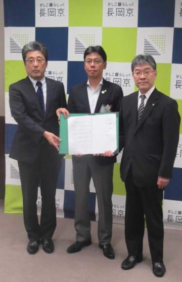 協定書に調印した中小路市長(中央)ら=長岡京市役所