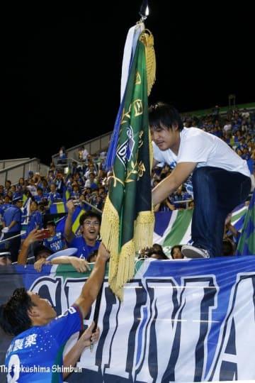 写真を拡大 1-0で愛媛に競り勝ち、ダービーフラッグをサポーターへ手渡す徳島の岩尾(左下)=松山市のニンジニアスタジアム