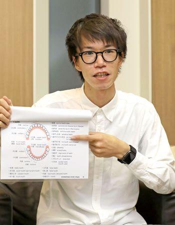 翻訳冊子を指さし、使い方を説明する古山正裕さん=新潟市中央区