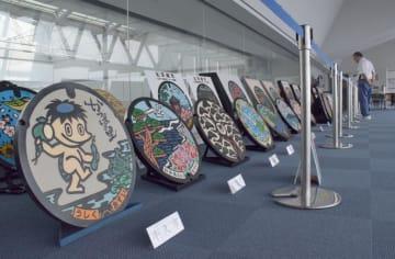 特色豊かなマンホールふたが並ぶ展示=県庁