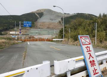 熊本地震で国道57号の寸断や阿蘇大橋の崩落が起きた土砂崩れ現場(奥)=4月、熊本県南阿蘇村