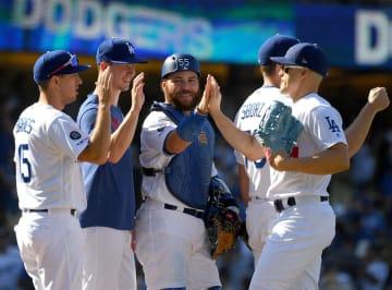 ジャイアンツ戦に勝利し、ハイタッチを交わすドジャースの選手たち=8日、ロサンゼルス(ゲッティ=共同)