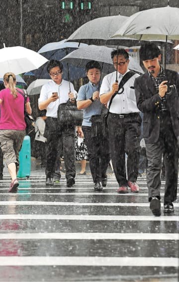 台風の影響で時折激しい雨が降る中、通勤する人たち=9日午前8時40分ごろ、仙台市青葉区中央1丁目