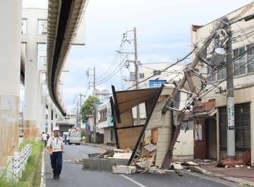 2階建て建物の屋上にあった物置が崩れ落ち、電柱も折れた。強風の影響とみられ、周囲は通行止めとなった=9日午前9時15分ごろ、千葉市稲毛区作草部